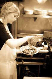 young ponytailed blonde chef helper adding sauce to dish - photo taken at Angelo's Ristorante Cda